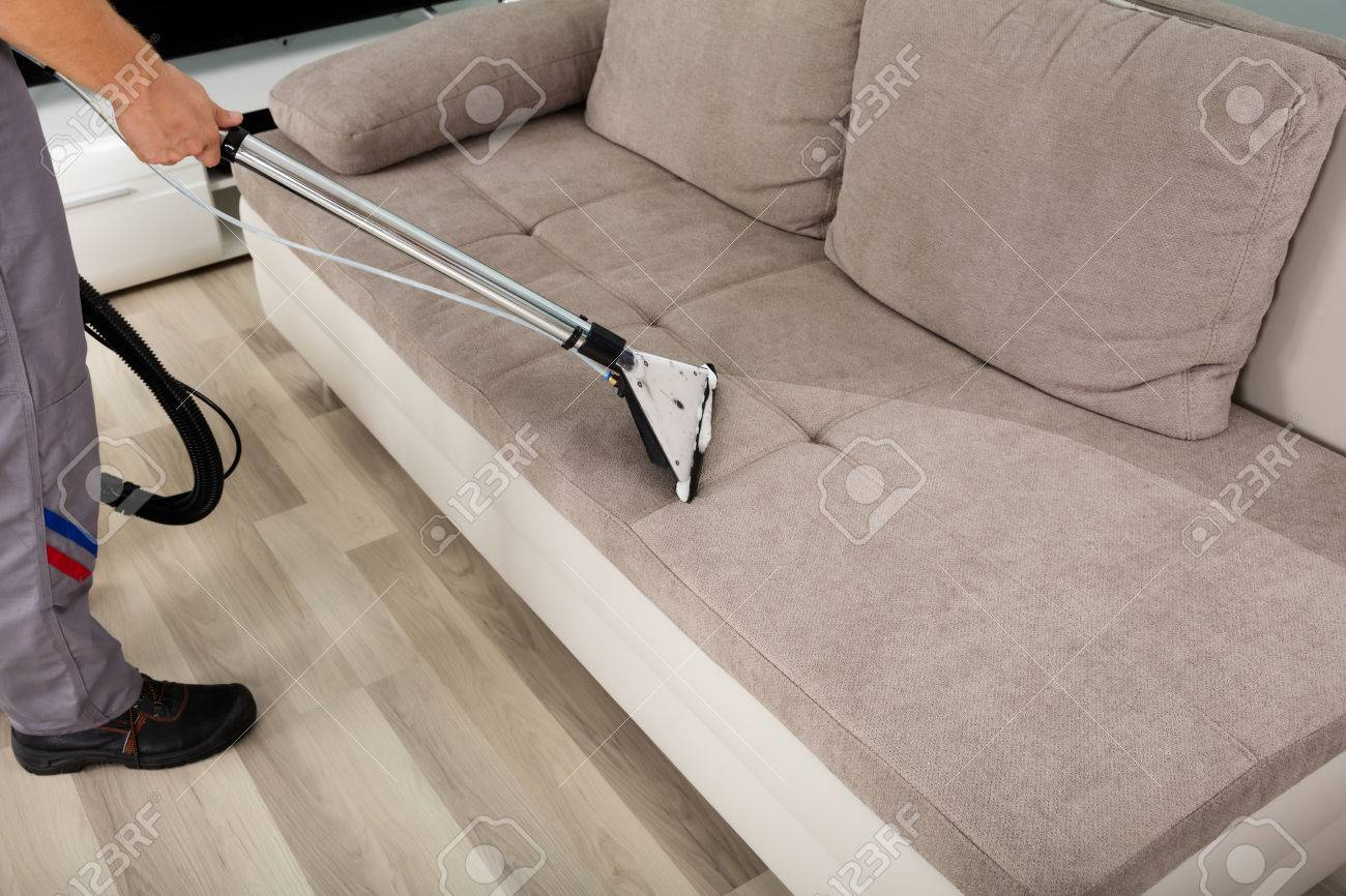 Stock Photo   Young Male Worker Cleaning Sofa With Vacuum Cleaner