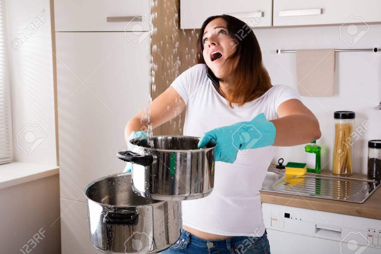 Femme Shocked Calling Plumber Bien que la collecte d'eau Fuite De Plafond En utilisant Ustensile Banque d'images - 69612789