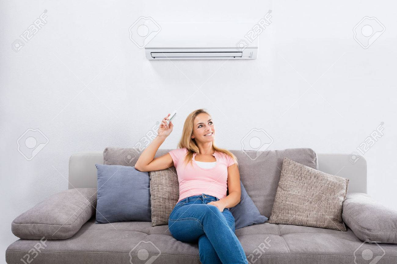 Young Happy Woman Sitting On Couch Operating Air Conditioner With Remote Control At Home Standard-Bild - 69612812