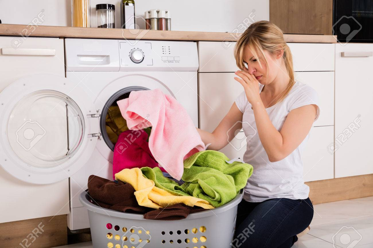 Young Woman Looking At Smelly Clothes Out Of Washing Machine In Kitchen Standard-Bild - 70308541