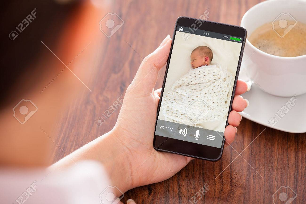 Close-up Of Person Hand Looking At Baby On Babyphone Standard-Bild - 70448563