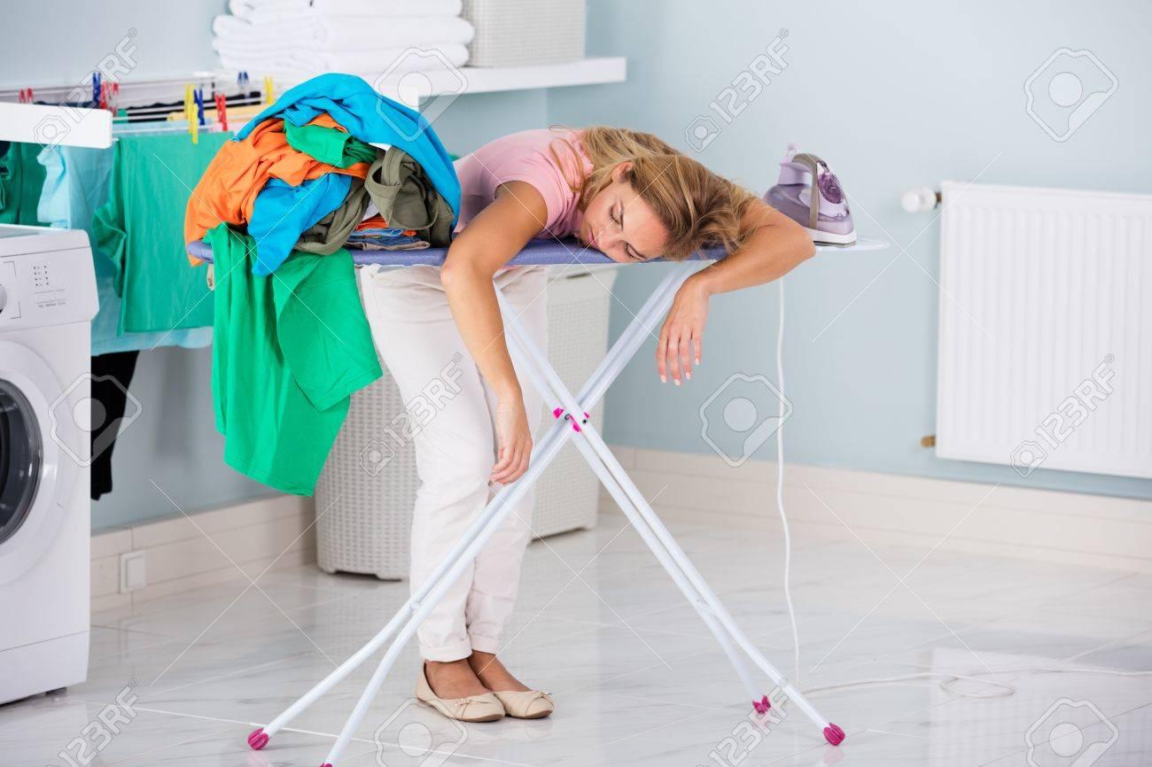 Fatigué jeune femme dormir sur table à repasser Next To pile de vêtements At Home Banque d'images - 70455290
