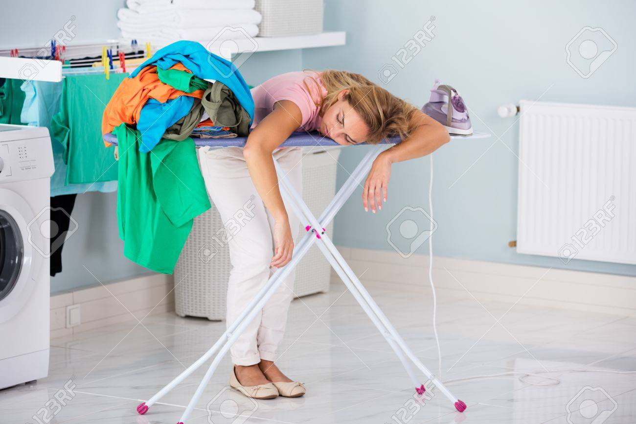 Young Tired Woman Sleeping On Ironing Board Next To Pile Of Clothes At Home Standard-Bild - 70455290