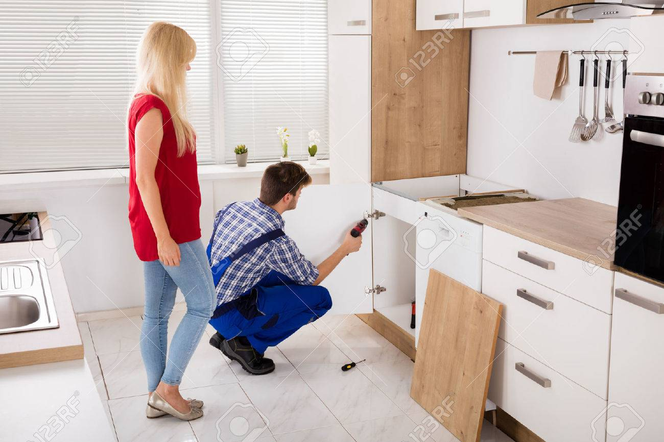 Repairman Fixing Or Installing The Furniture Door Of The Kitchen Sink In Front Of Woman Standard-Bild - 70455573