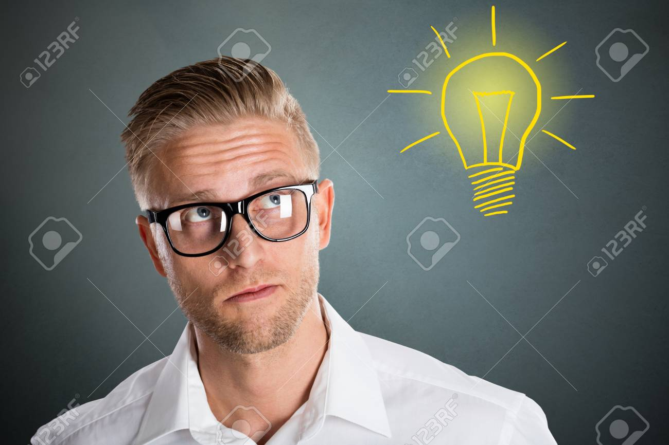 Smart Young Man With Thoughtful Expression Light Bulb Idea On Grey Background Stock Photo