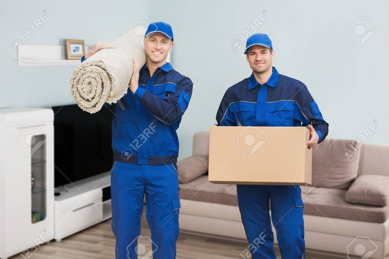 Portrait Of A Two Male Movers Carrying Rolled Carpet And Cardboard Box In House Standard-Bild - 70824262