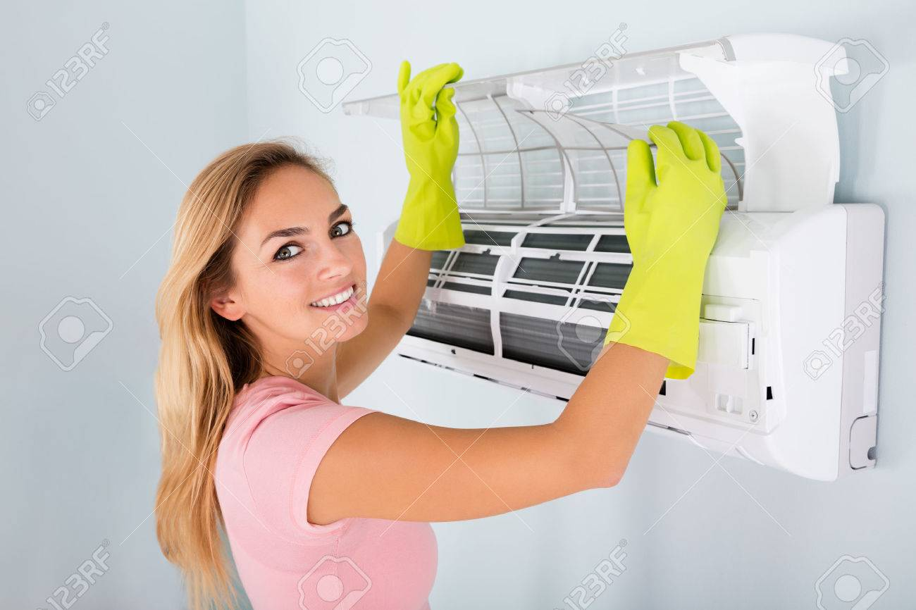 young woman checking and cleaning air conditioning system at.. stock
