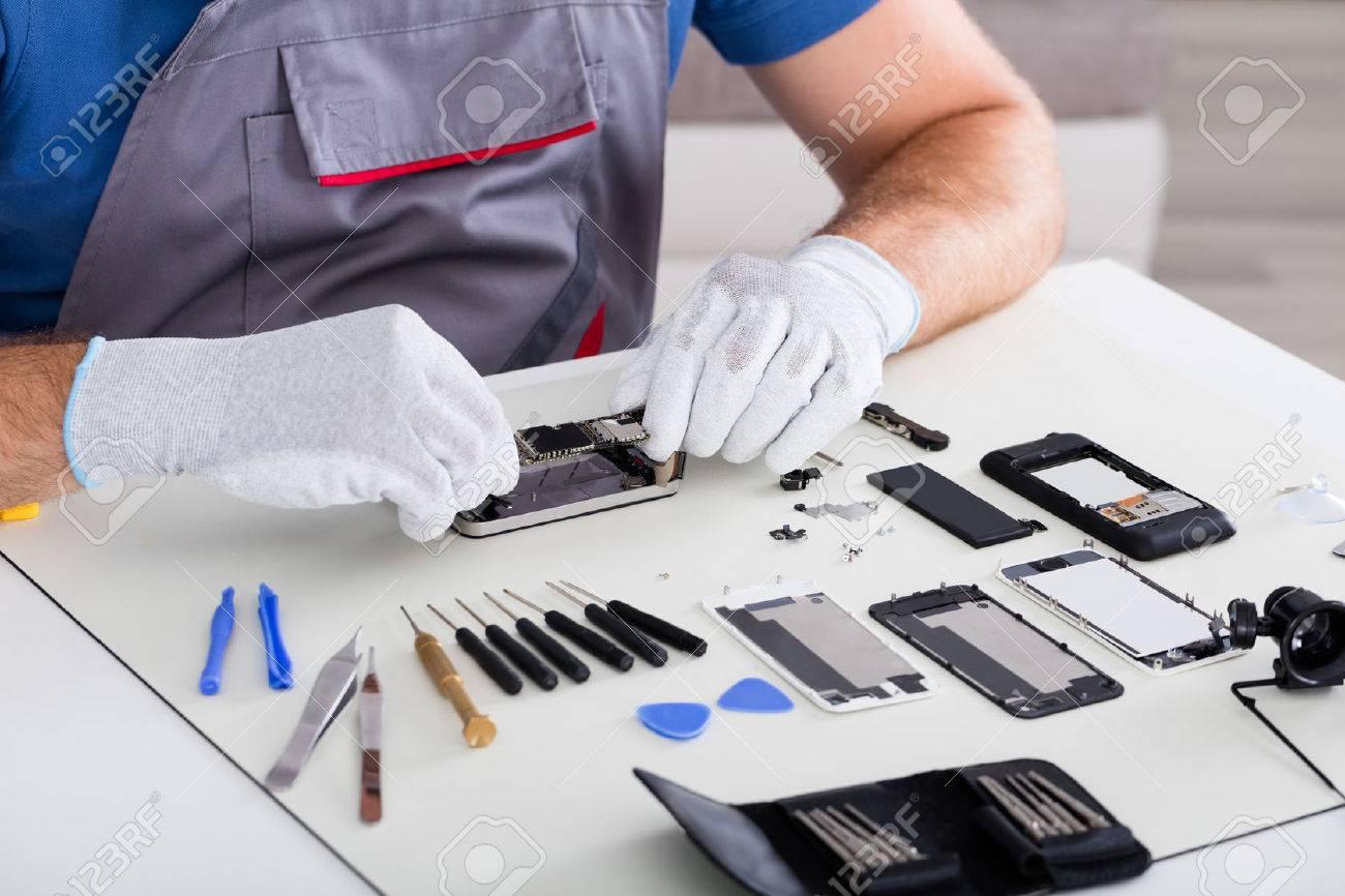 b76d790033b Foto de archivo - Primer plano de la mano de la persona llevaba guantes de  Reparación Celular con un destornillador