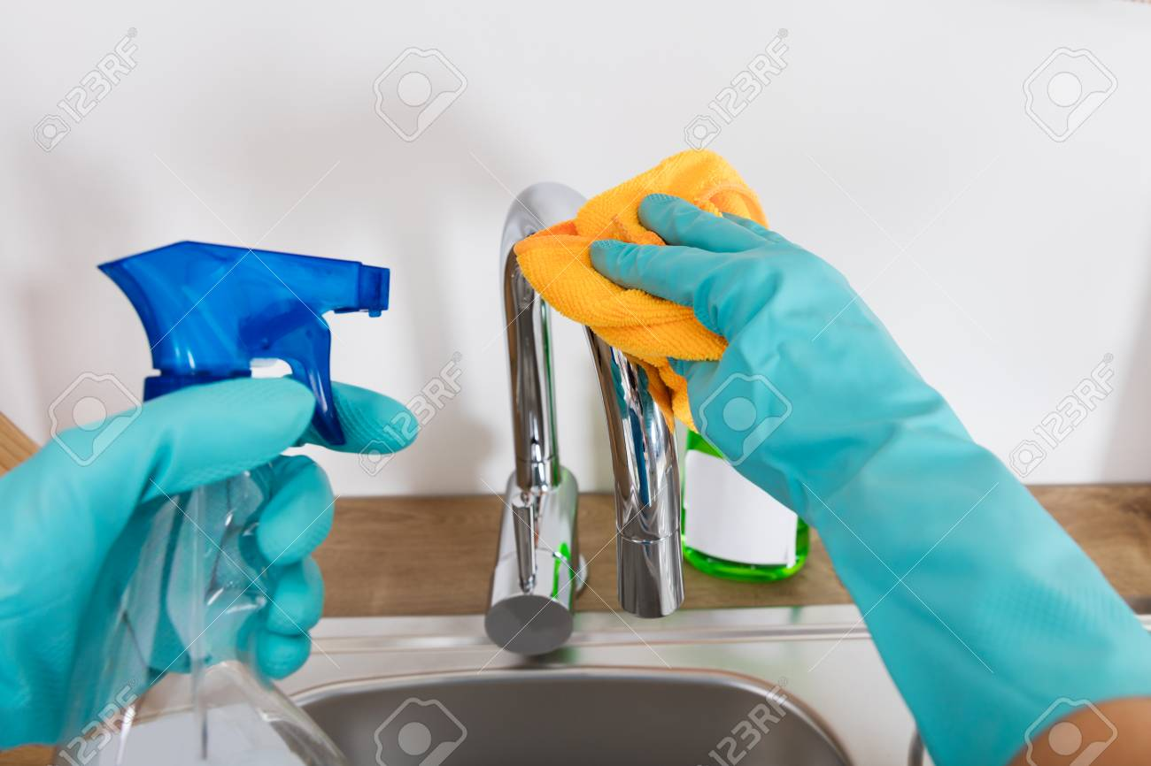 Person Cleaning Sink Tap In The Kitchen With Cloth And Spray.. Stock ...