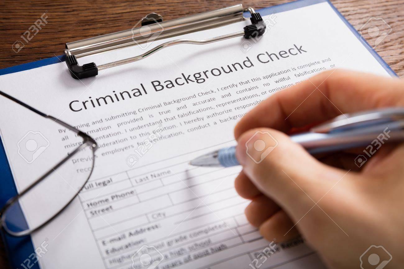 Gros plan de remplissage des antécédents criminels Formulaire de vérification de l'application de la personne à la main Banque d'images - 71451566