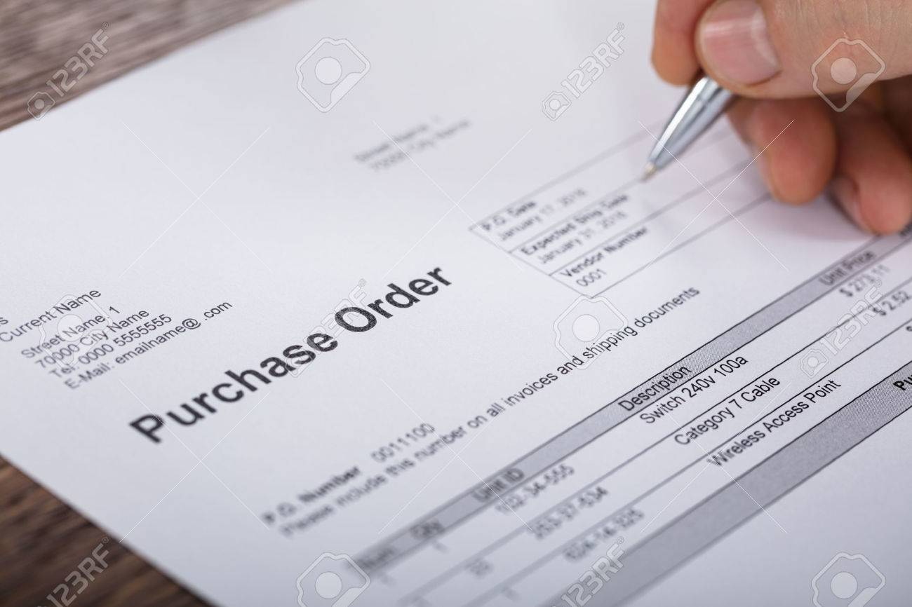 Close-up Of A Person Hand Filling A Purchase Order Form On Wooden Desk Standard-Bild - 72006495