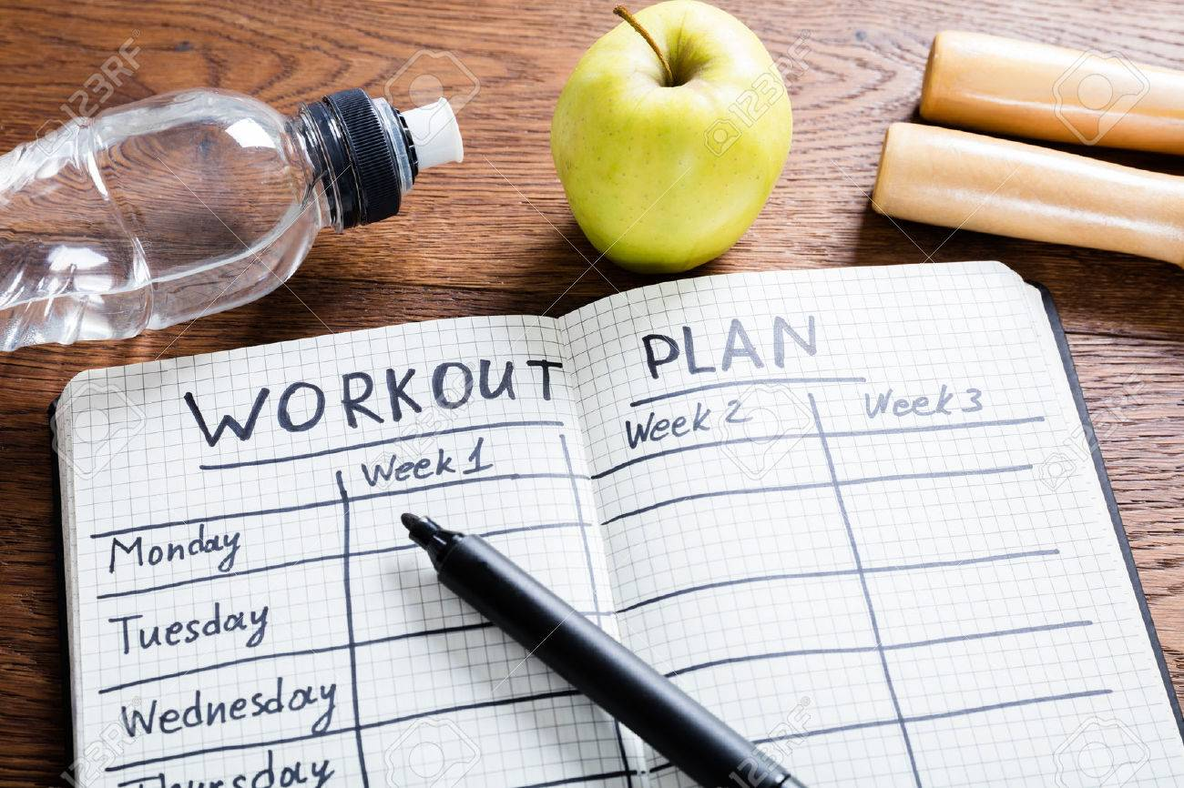 High Angle View Of A Workout Plan In Notebook At Wooden Desk - 72006561