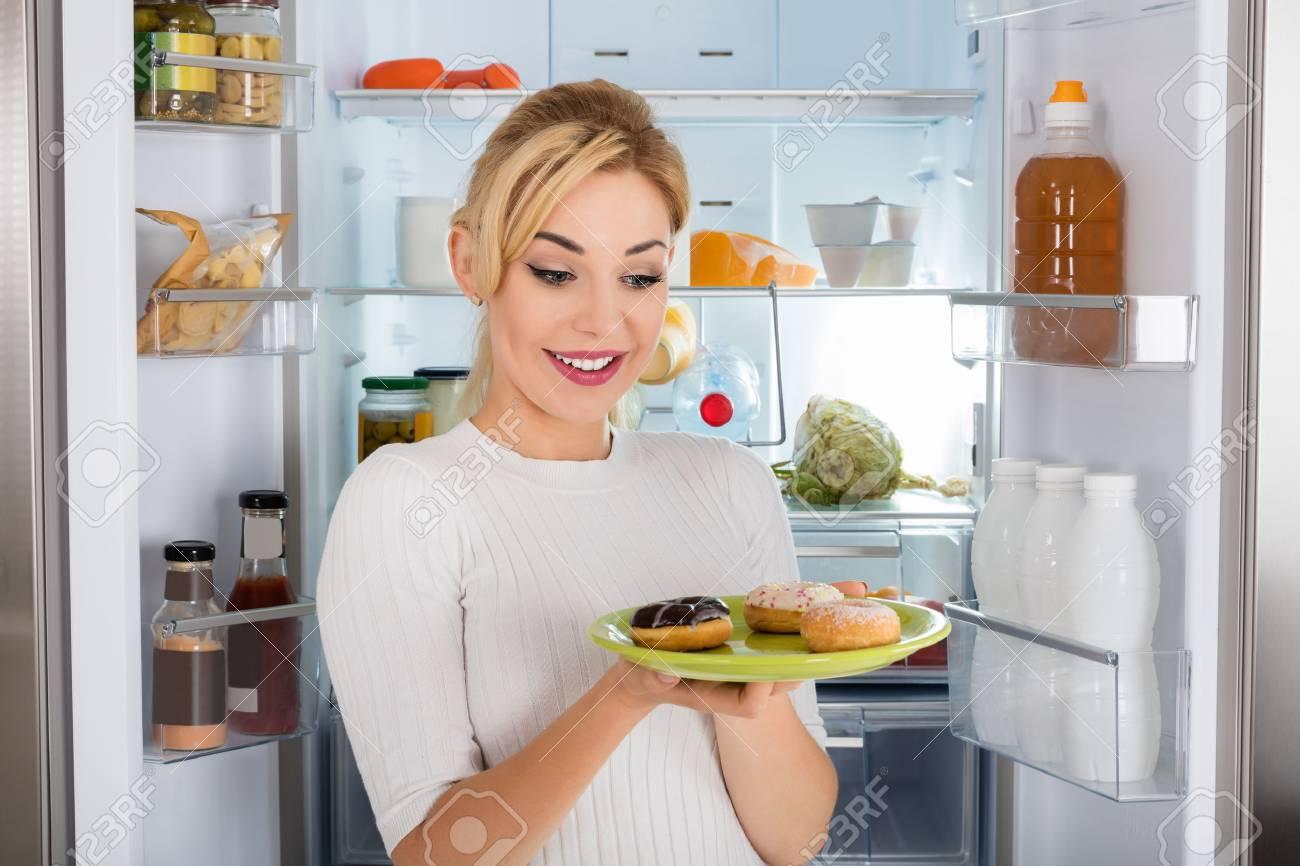 Kühlschrank Platte : Junge frau die in der nähe kühlschrank essen donut von der platte