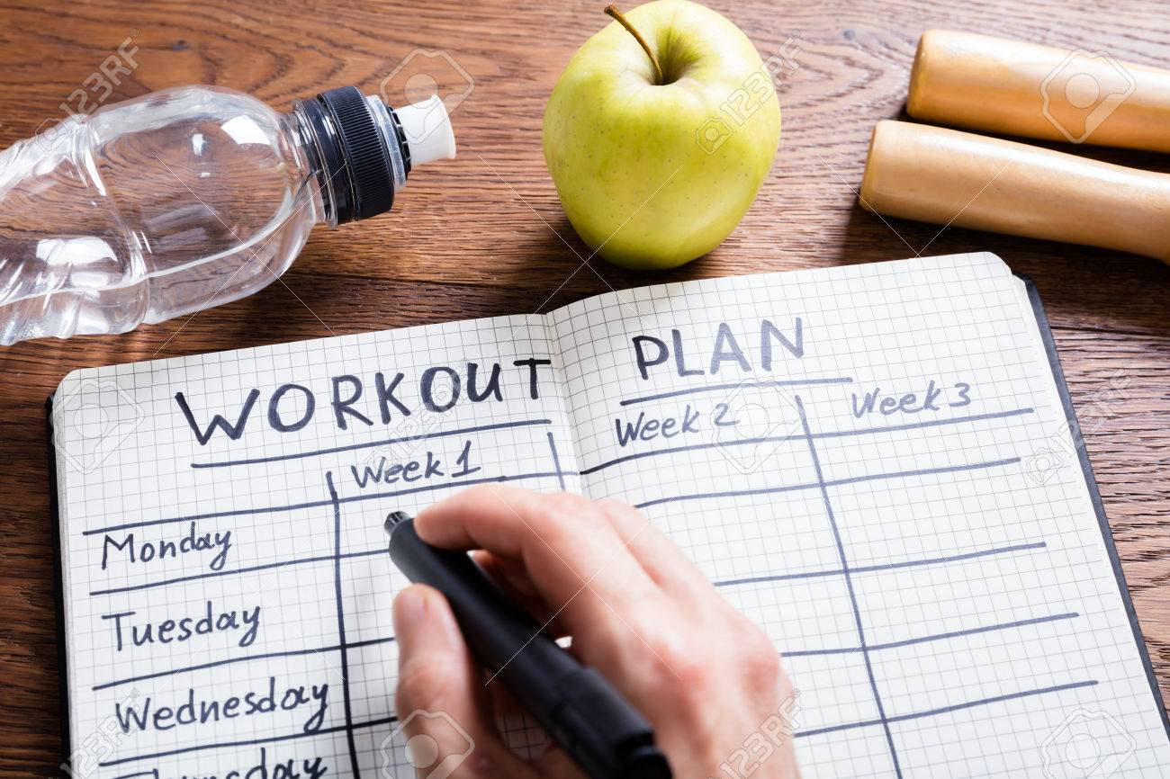 High Angle View Of A Workout Plan In Notebook At Wooden Desk Standard-Bild - 72570570