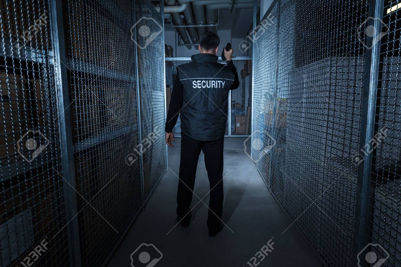 Rear View Of A Security Guard Standing In The Warehouse Holding Flashlight Standard-Bild - 72570581