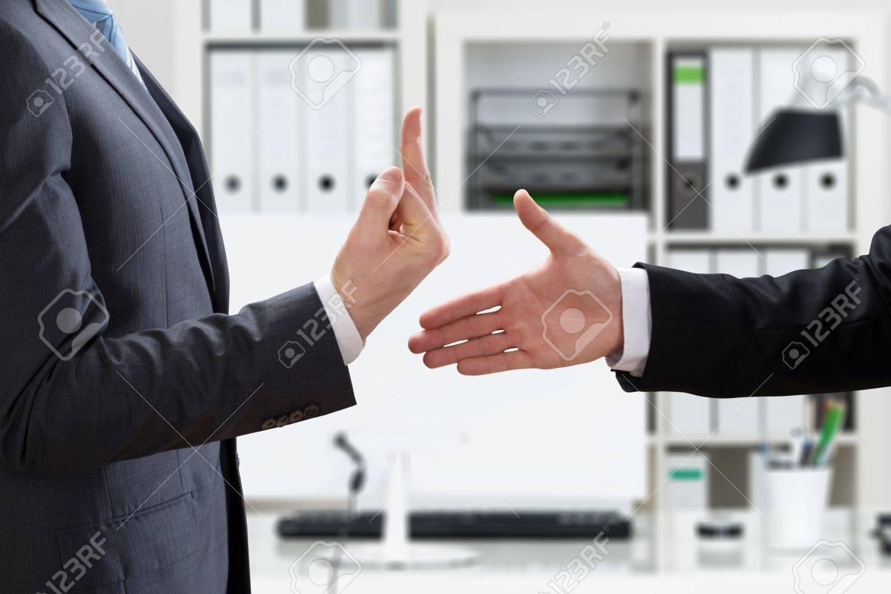 72570329-close-up-of-a-businessman-showing-middle-finger-to-partner-offering-handshake-in-office.jpg