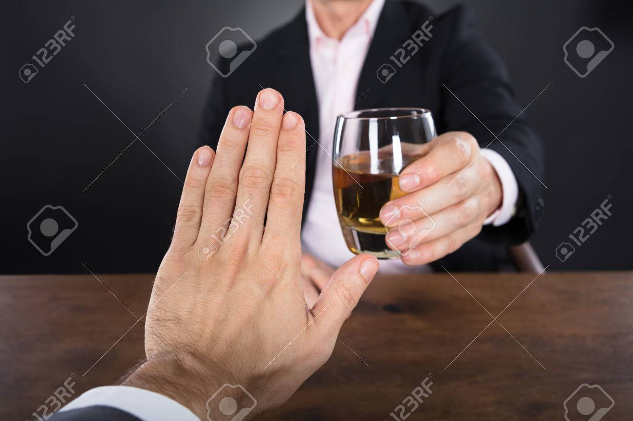 Businessman Hand Rejecting A Glass Of Whiskey Offered By Businessperson Standard-Bild - 72565267