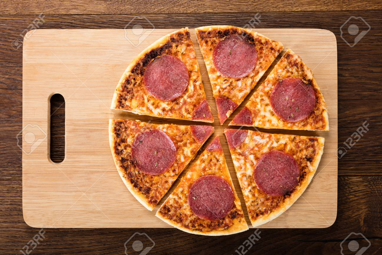 Slices Of Delicious Homemade Salami Pizza On Chopping Board Stock Photo - 75949127