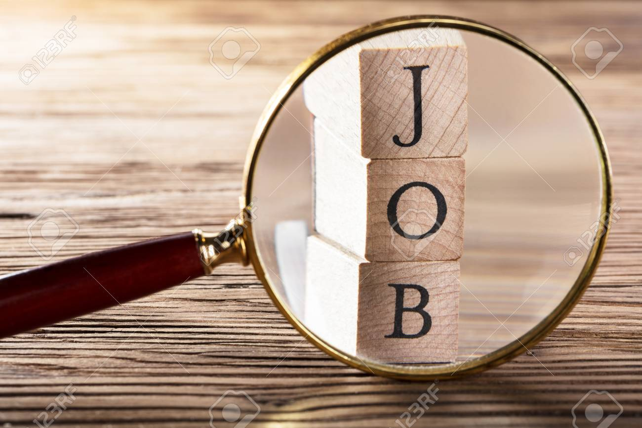 Close-up Of Job Block Seen Through Magnifying Glass On Wooden Table - 81079231