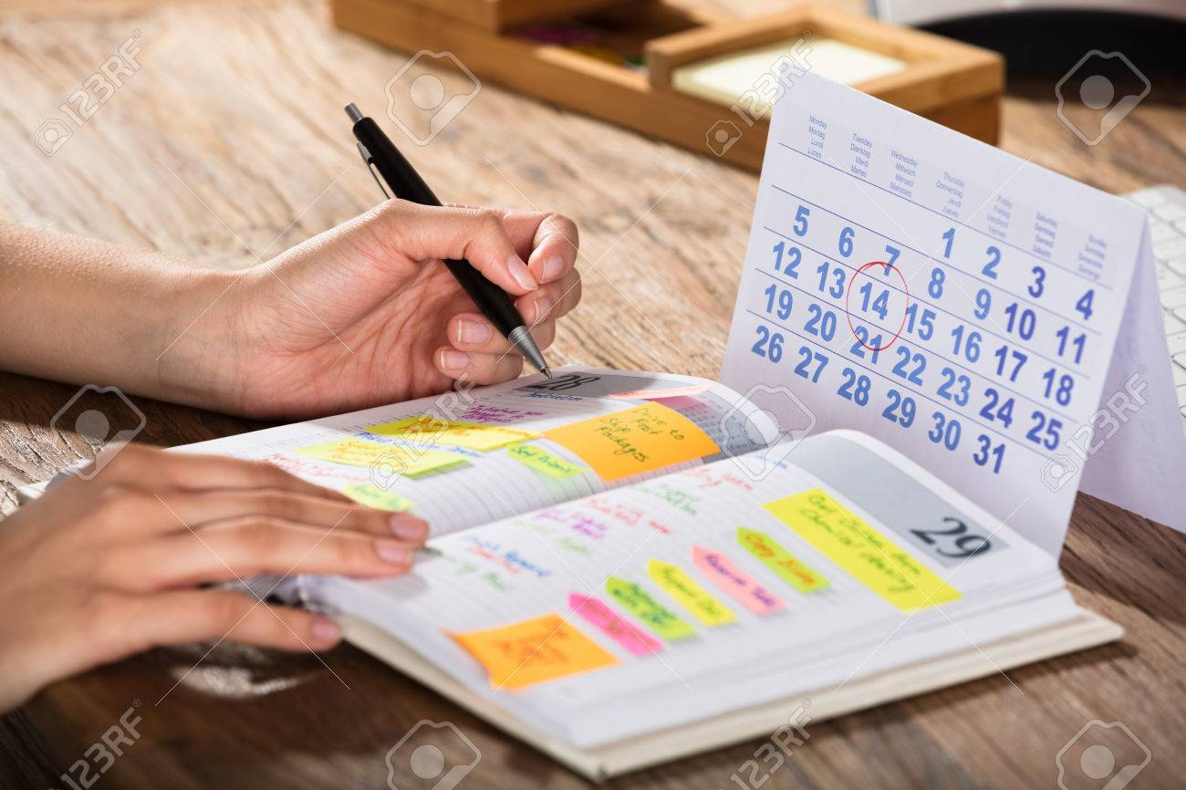 Close-up Of A Businessperson With Calendar Writing Schedule In Diary On Desk - 76970314