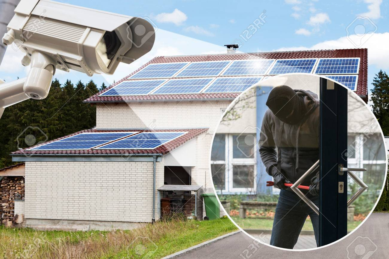 CCTV Camera Showing Burglar Trying To Open A Door Lock In Front Of House Stock Photo & CCTV Camera Showing Burglar Trying To Open A Door Lock In Front ...