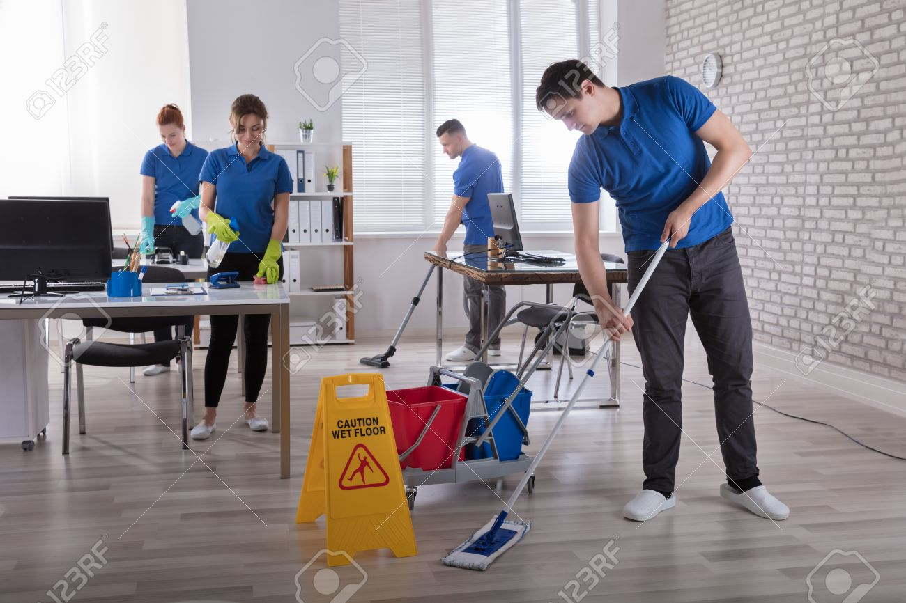 Group Of Janitors Cleaning The Modern Office With Caution Wet Floor Sign Stock Photo