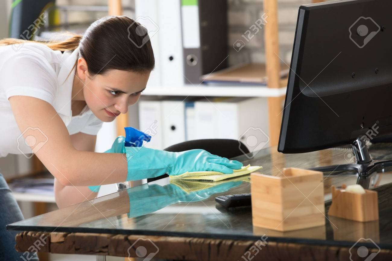 Happy Young Woman Cleaning The Glass Office Desk With Rag - 82938234