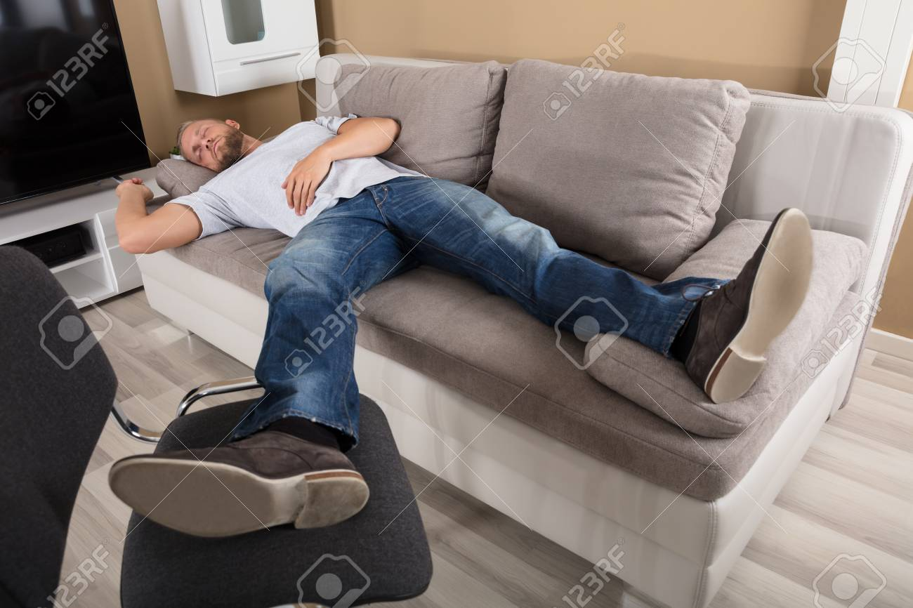 Young Man Sleeping On Couch In Living Room