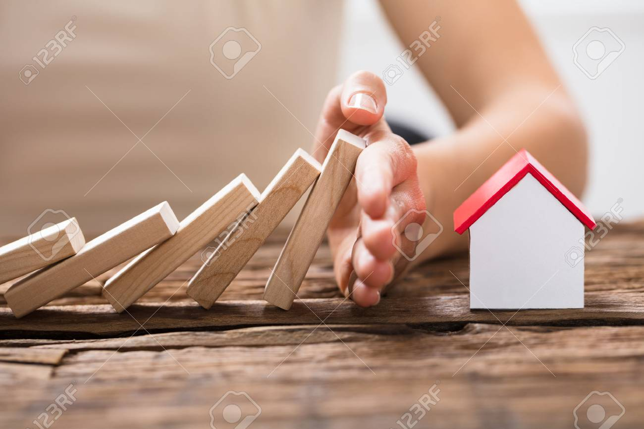 Close-up Of A Human Hand Stopping The Wooden Blocks From Falling On House Model - 84588021