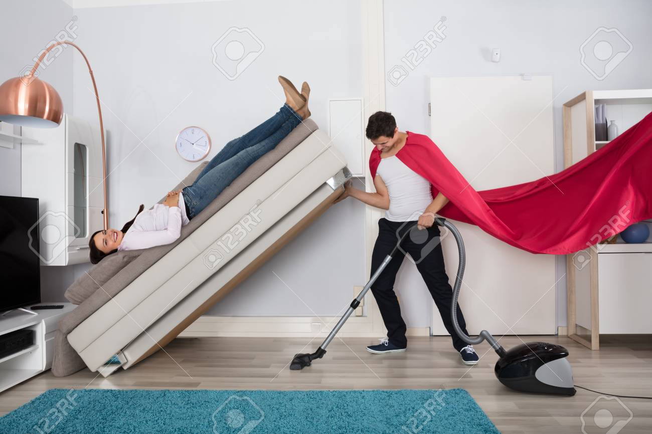 Superior Stock Photo   Young Man Wearing Red Cape Cleaning Under The Couch With  Vacuum Cleaner