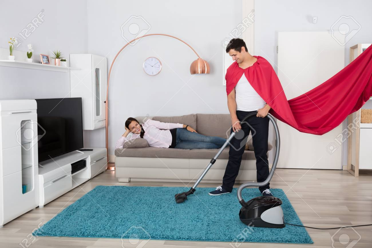Happy Woman Lying On Sofa Looking At Her Husband Cleaning Carpet With Vacuum  Cleaner Stock Photo
