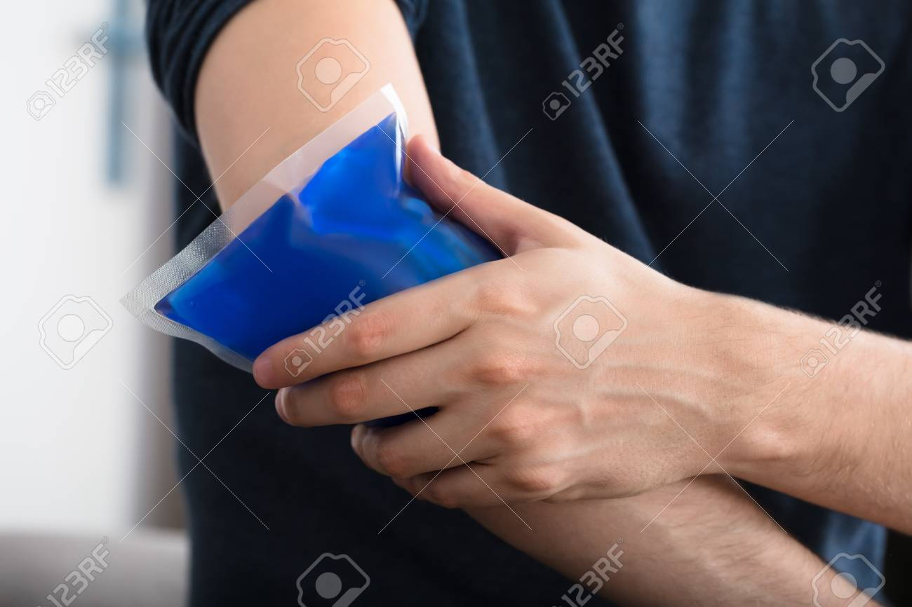 Close-up Of A Person Applying Ice Gel Pack On An Injured Elbow At Home - 87896047