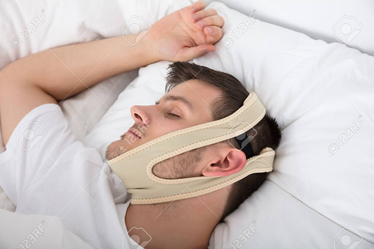 Young Handsome Man Sleeping With Anti Snoring Chin Strap On Head