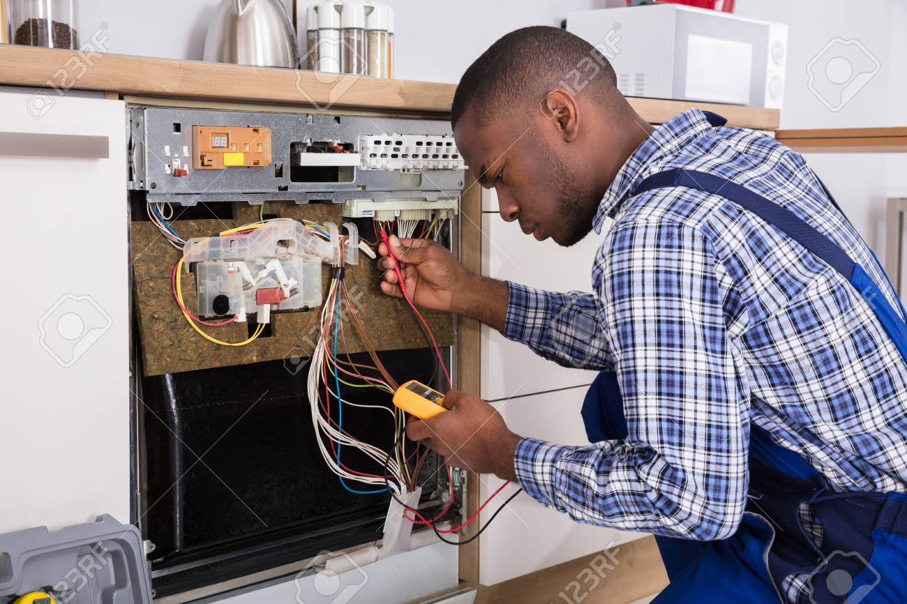Young Male African Technician Fixing Dishwasher With Digital Multimeter In Kitchen - 92338601