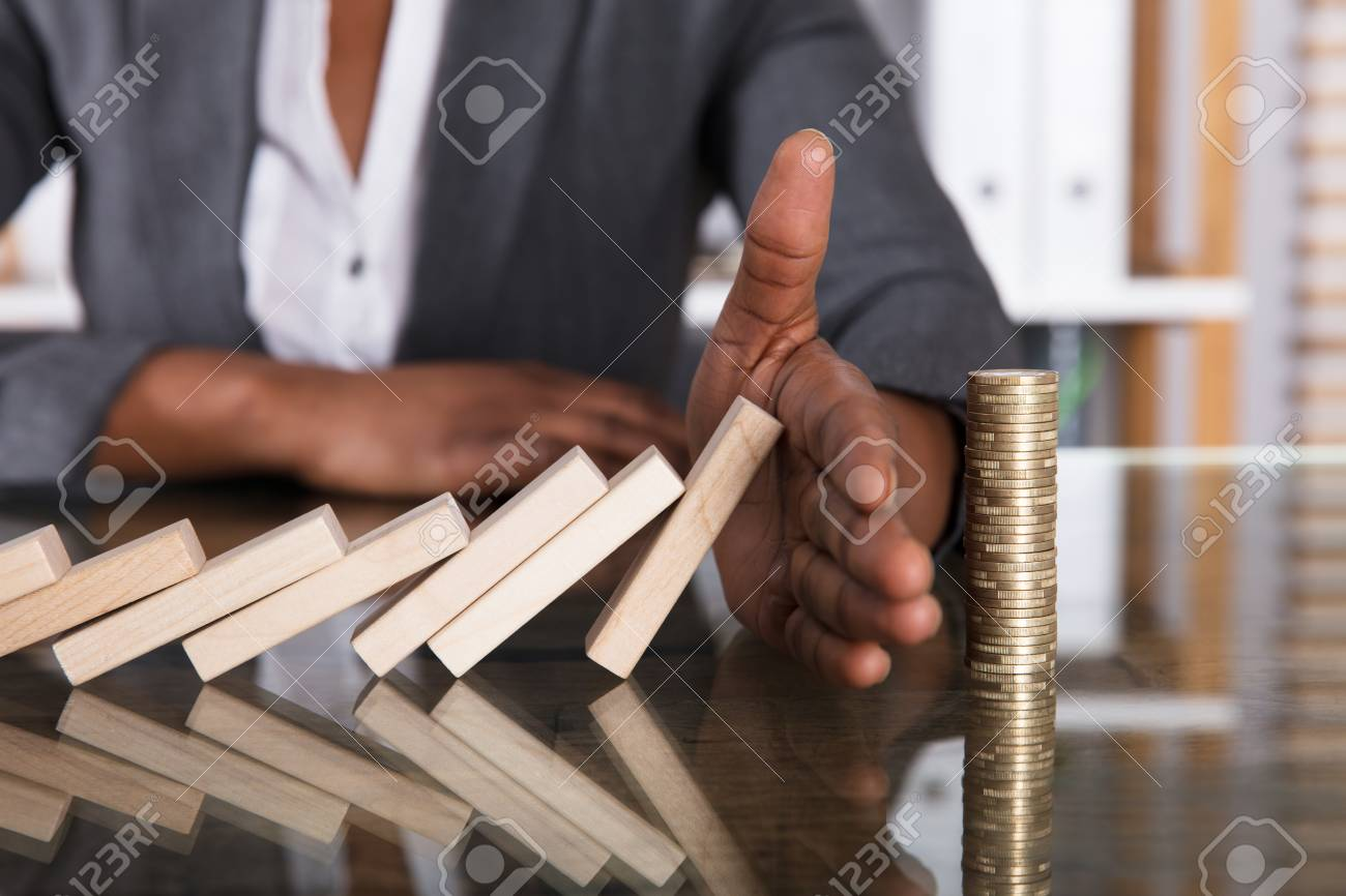 Close-up Of A Human Hand Stopping Wooden Blocks From Falling On Stacked Coins Over Desk - 92338874
