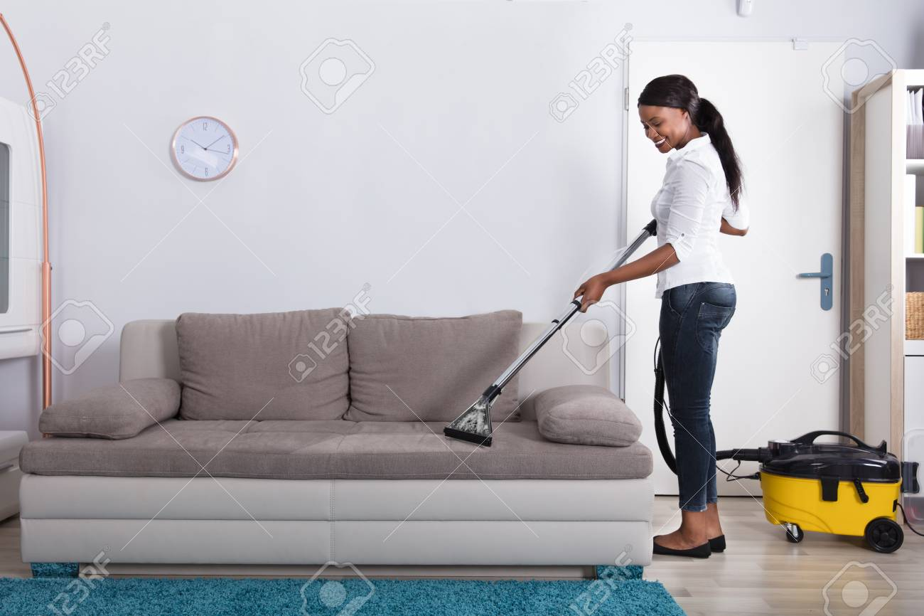 Charming Happy Young African Woman Cleaning Sofa With Vacuum Cleaner At Home Stock  Photo   92352441