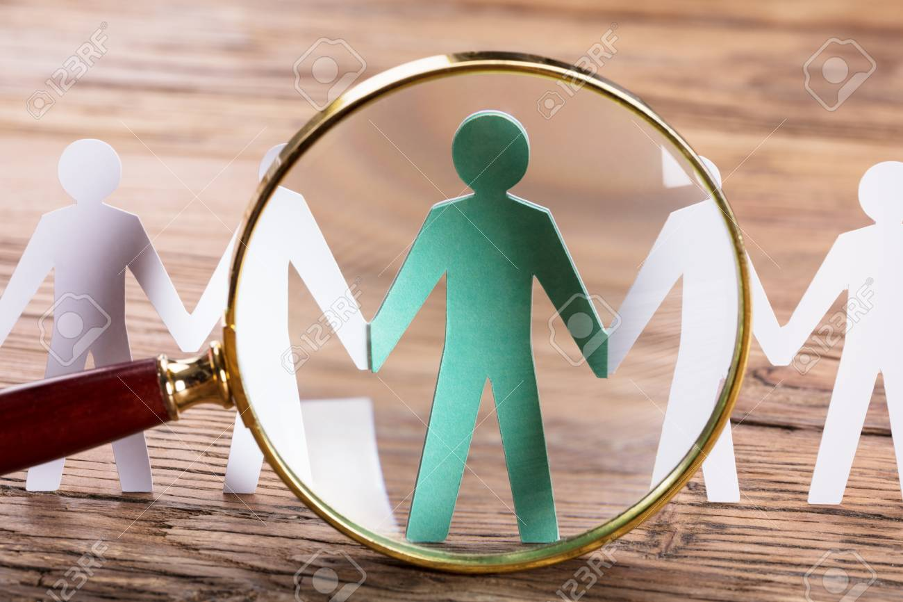 Magnifying Glass On Cut-out Figures On Wooden Desk - 90439523