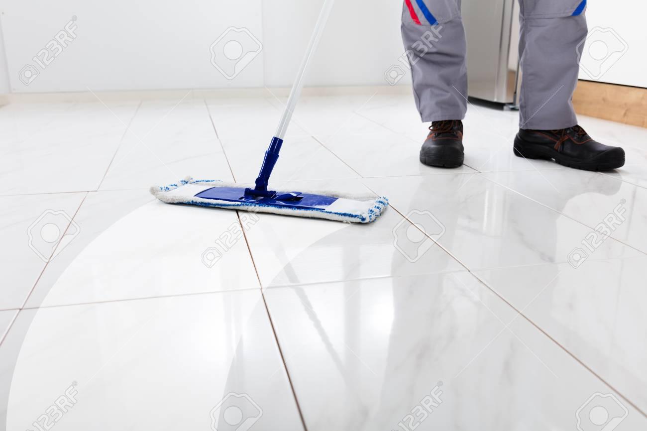Travailleur à laver le sol avec une vadrouille dans la cuisine