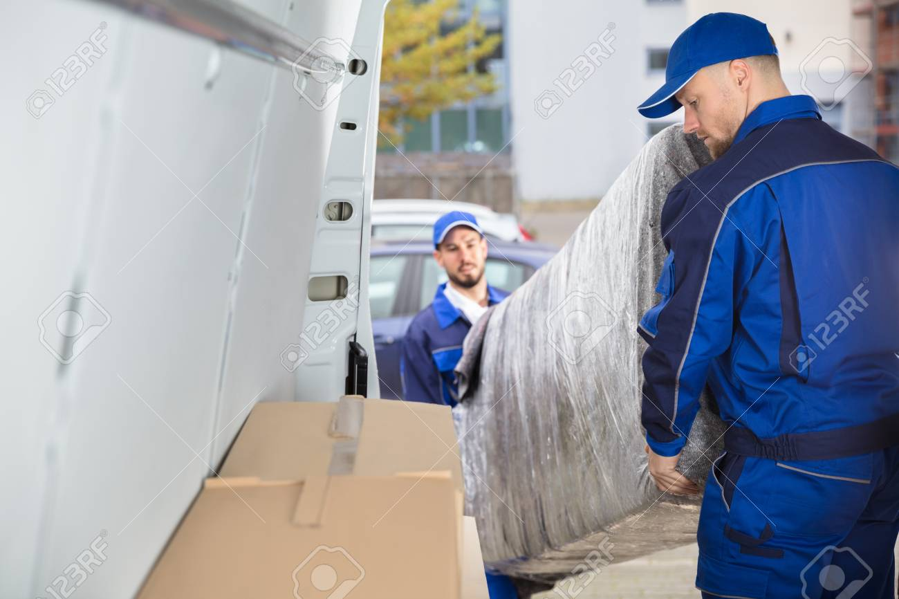 Two Happy Male Movers In Uniform Unloading Furniture From Truck - 92390423