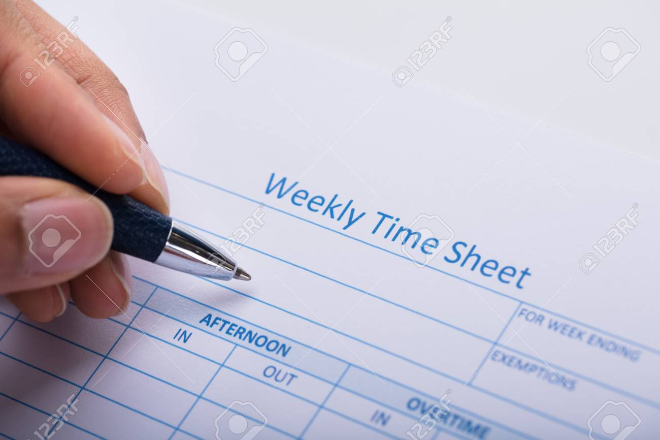 close up of a person s hand filling blank weekly time sheet with