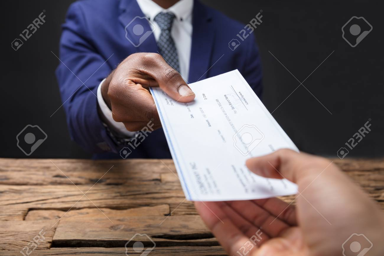 Close-up Of A Businessman's Hand Giving Cheque To Colleague Over Wooden Desk - 93552990