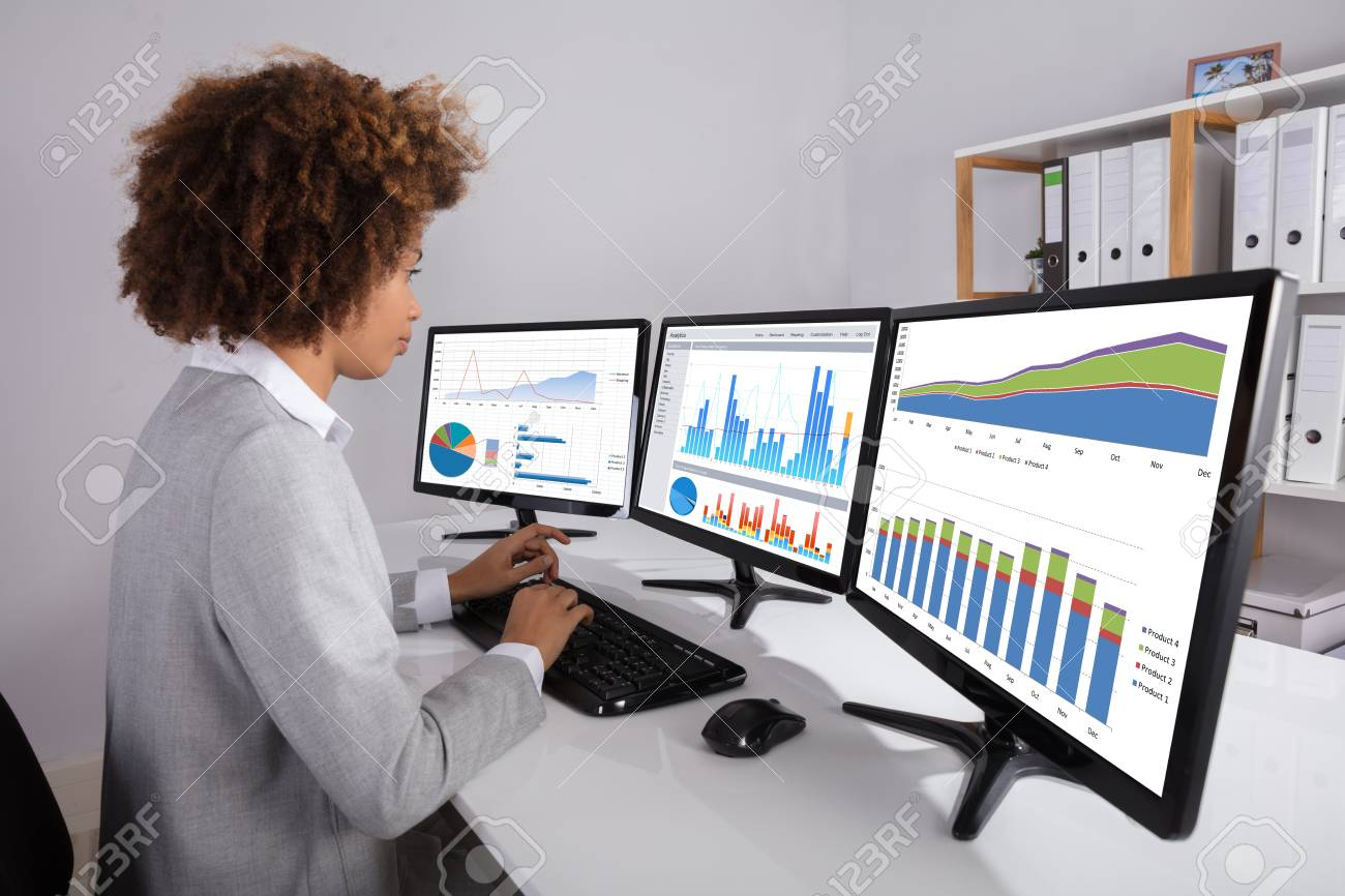 Businesswoman Analyzing Graph On Multiple Computers On Desk In Stock Photo Picture And Royalty Free Image Image 93986855