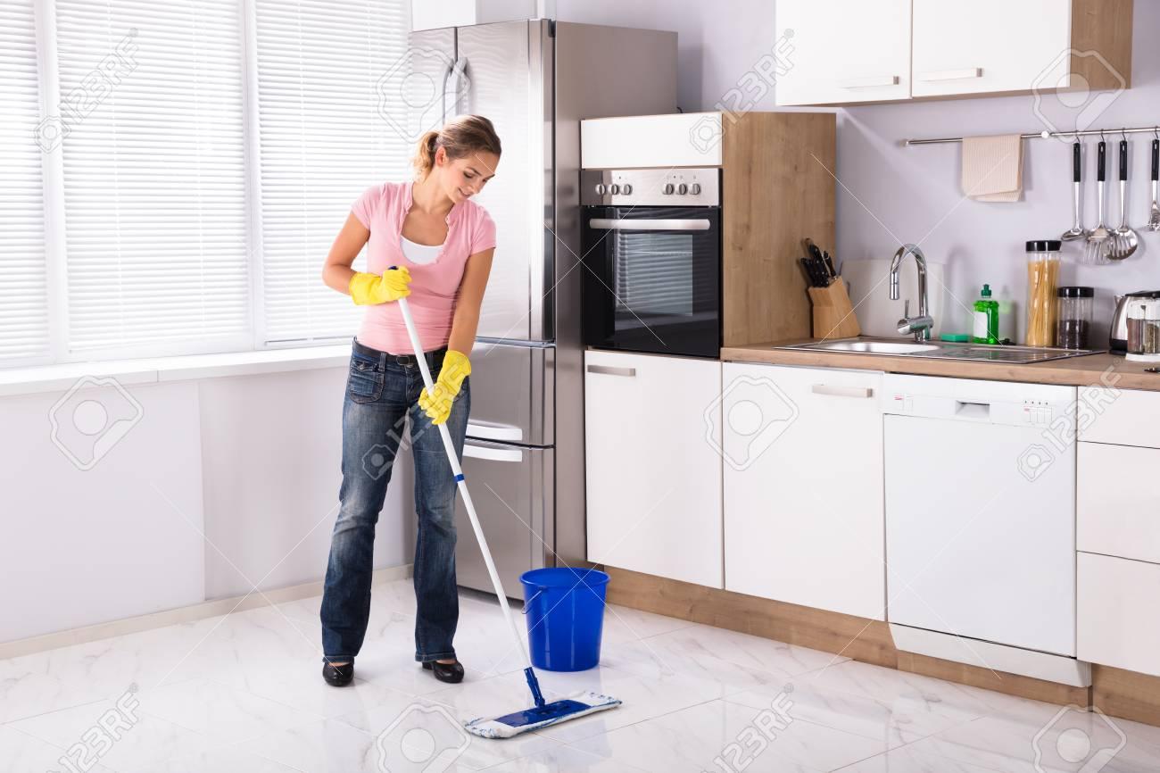 Lächelnde Junge Frau Reinigung Küche Boden Mit Mop In Der Küche Zu ...