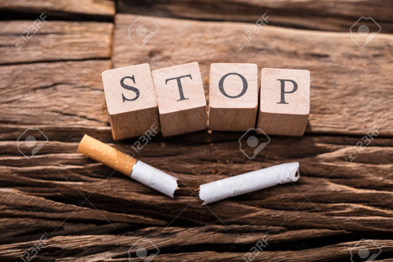 Close-up Of A Cigarette And Wooden Blocks Showing Stop Word On Desk - 93783334
