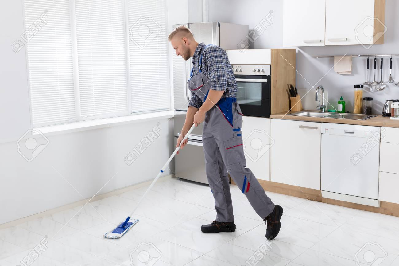 Happy Young Male Worker Mopping Floor With Mop In Kitchen Stock ...
