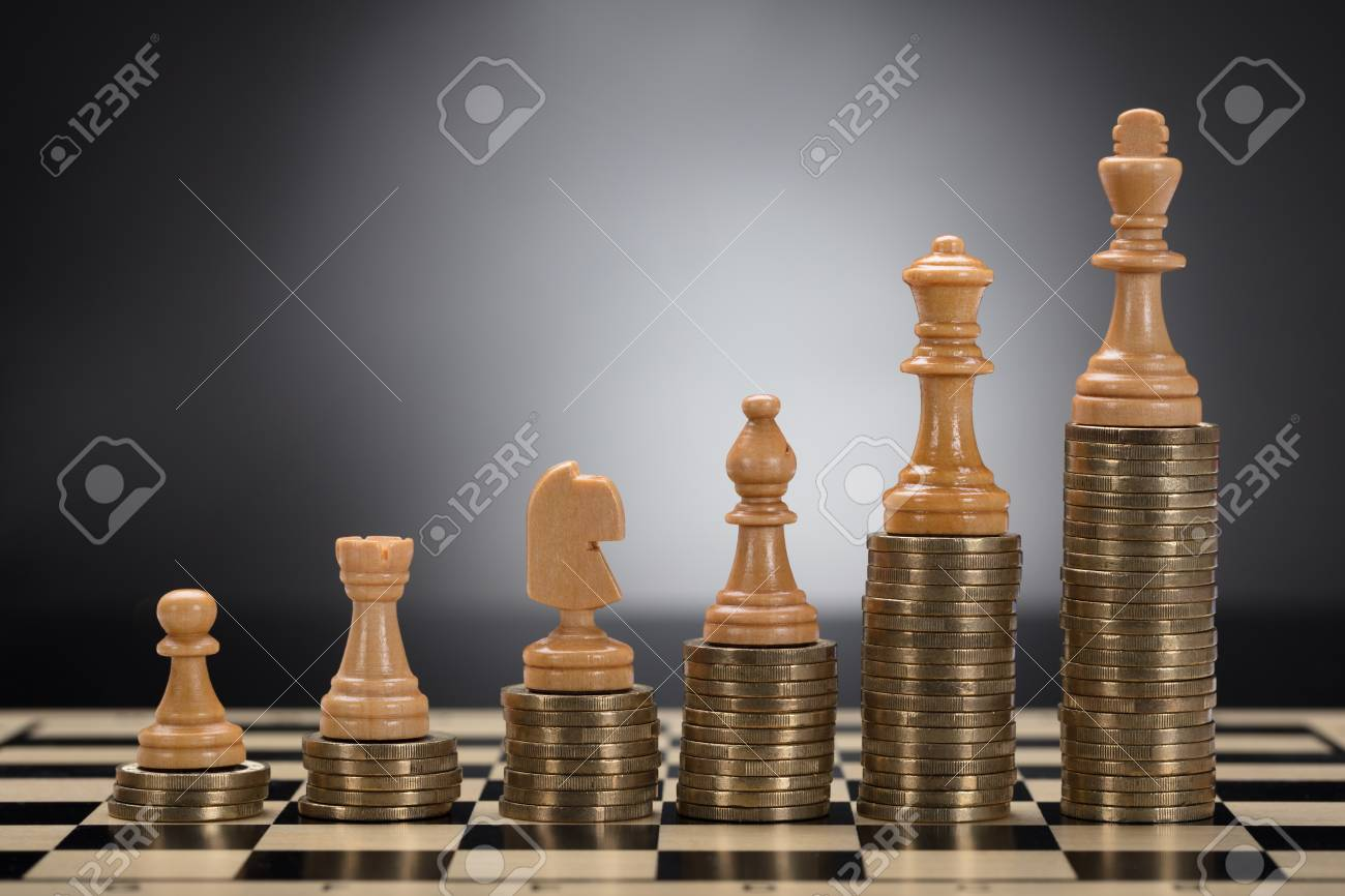 Close-up Of Chess Pieces On Stacked Golden Coins Against Grey