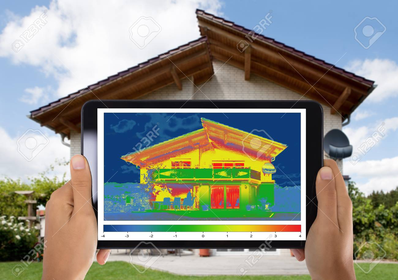 Close-up Of Person Detecting Heat Loss Outside The House Using Digital Tablet - 94426789