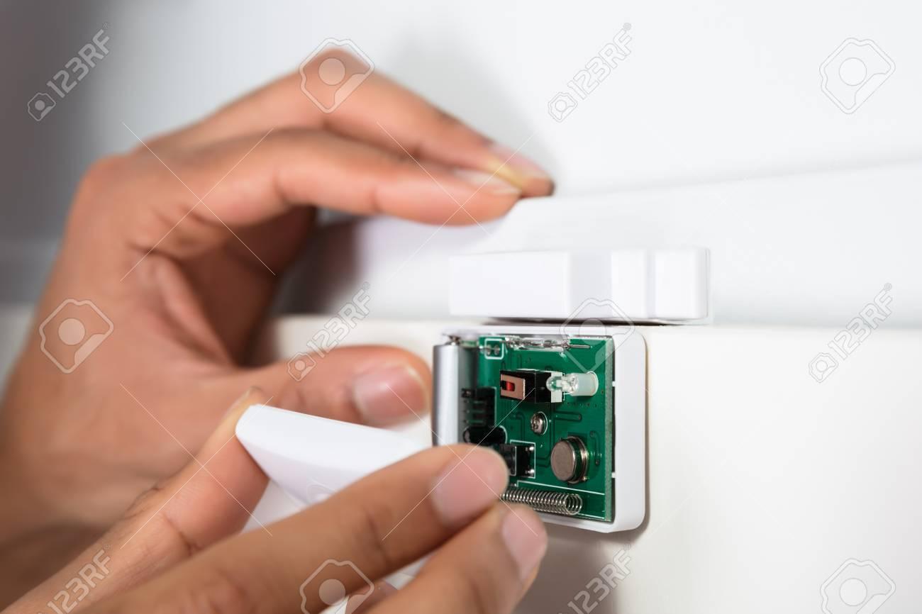Close-up Of A Technician's Hand Repairing Security System Door