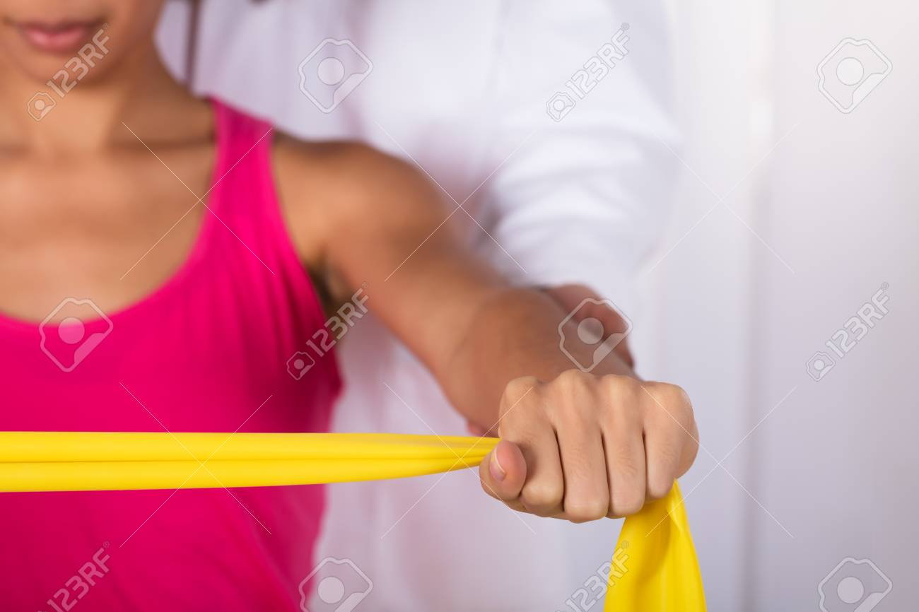 Physiotherapist Assisting Woman While Exercising With Exercise Band - 95089595