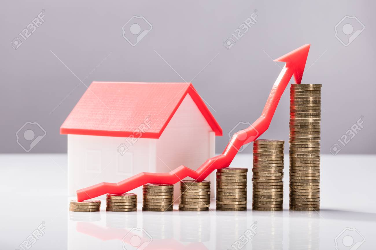 Close up of increasing graph of coins and house model on white close up of increasing graph of coins and house model on white desk stock photo ccuart Gallery